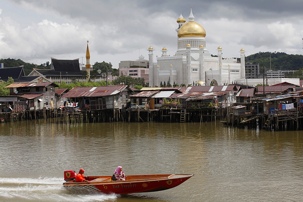 Boats past water village with Omar Ali Saifuddien mosque in Bandar Seri Begawan, Brunei, Southeast Asia, Asia