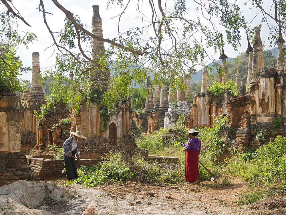 Local women cleaning area by old Buddhist temples in the Inle Lake region, Shan State, Myanmar (Burma), Asia
