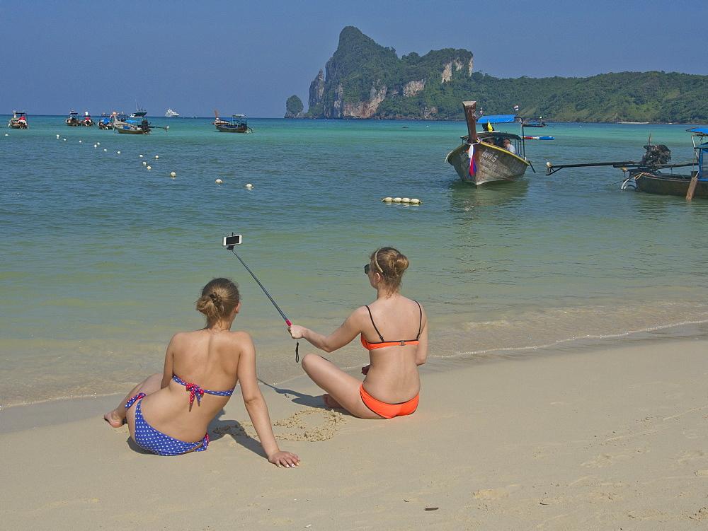 Western women tourists take selfie photo on beach at Phi Phi islands, Andaman sea, Thailand, Southeast Asia, Asia