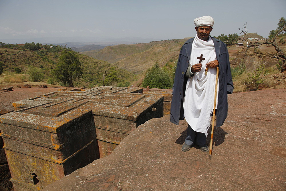 Orthodox priest hold cross at the ancient sunken rock-hewn church of St. George in Lalibela, Ethiopia, Africa