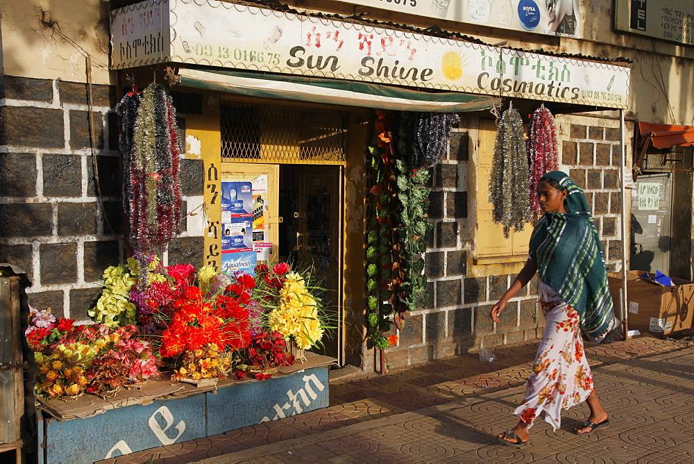 Woman in traditional dress walks in a shopping street in Bahir Dar, Ethiopia, Africa