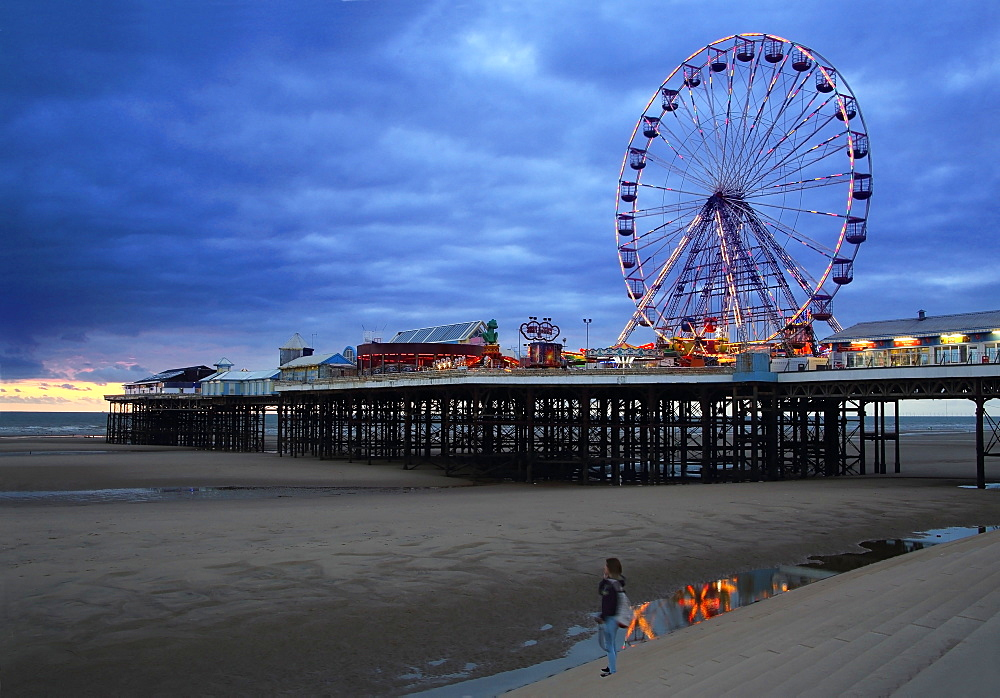 Big wheel and amusements on Central Pier at sunset with young women looking on, Blackpool, Lancashire, England, United Kingdom, Europe - 1191-40