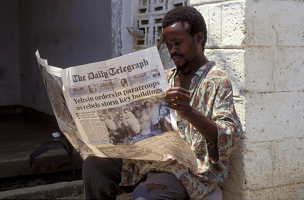 Man reading newspaper, zambia. Lusaka. He is reading the daily telegraph