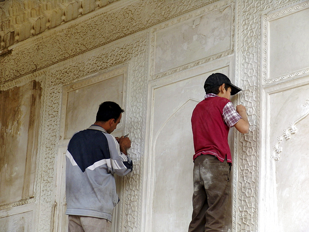 Uzbekistan craftsman and apprentice repairing the shah-i-zinda necropolis of mausoleums, samarkand