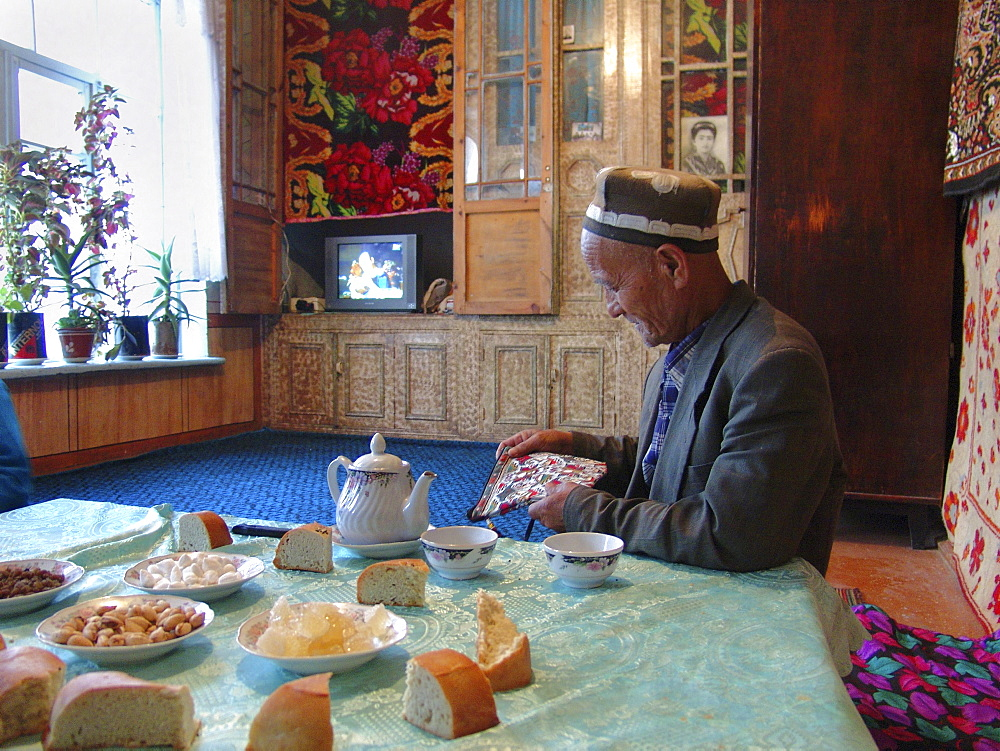 Uzbekistan man at home, table laid with tea, bread, sweets and nuts. Samarkand