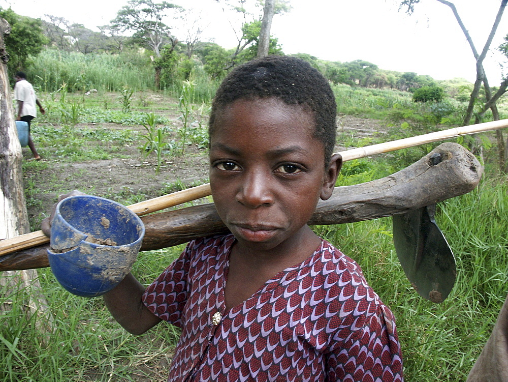 Zambia boy of kasisi carrying a hoe