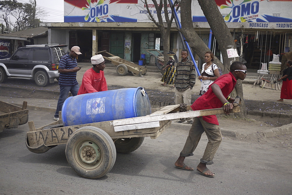 TANZANIA Man hauling a load of water, Arusha. photograph by Sean Sprague