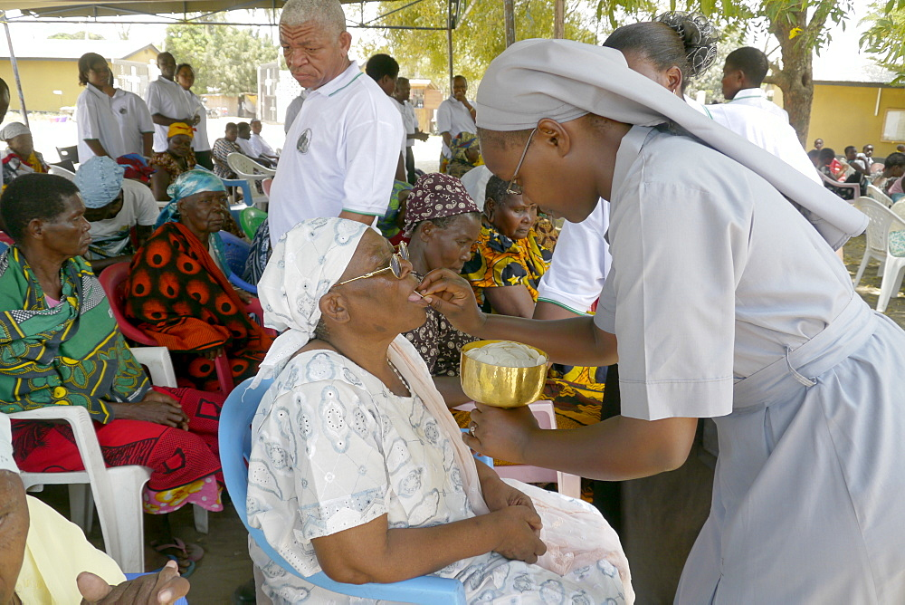 TANZANIA The Roman Catholic Parish of Buza, Dar es Salaam. Sunday mass. Nun giving sacrament to the sick sitting outside church. photograph by Sean Sprague