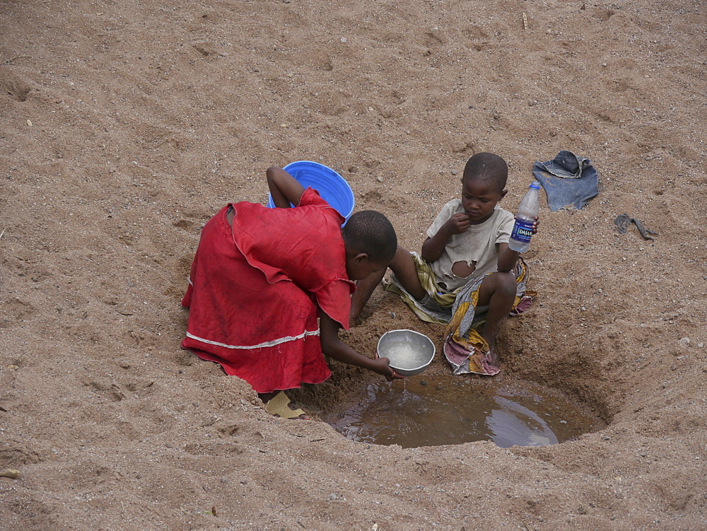 TANZANIA Children collecting water from a dried up river bed near Shinyanga. photograph by Sean Sprague