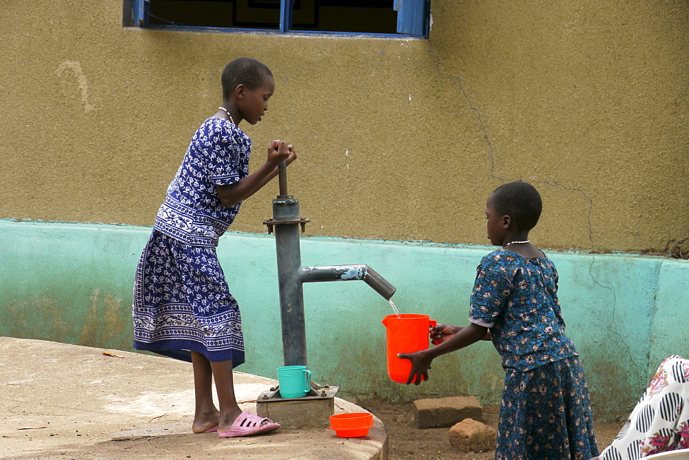 TANZANIA Home of Compassion, for the sick and needy, Kigera village, near Musoma. Girls collecting water from hand pump. photograph by Sean Sprague
