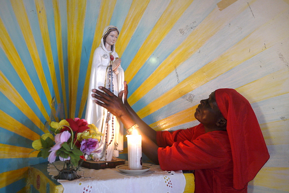 TANZANIA Home of Compassion, for the sick and needy, Kigera village, near Musoma. Nun in red habit adoring statue of mother Mary. photograph by Sean Sprague
