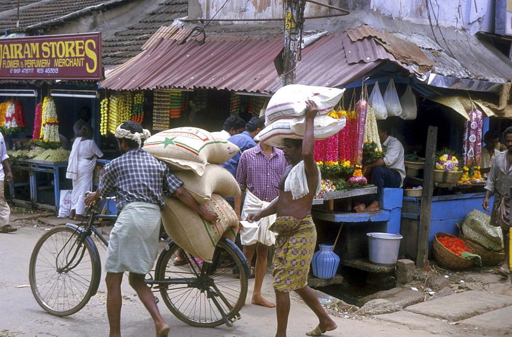 India - transportation carrying sacks of in a market street trivandrum, kerala