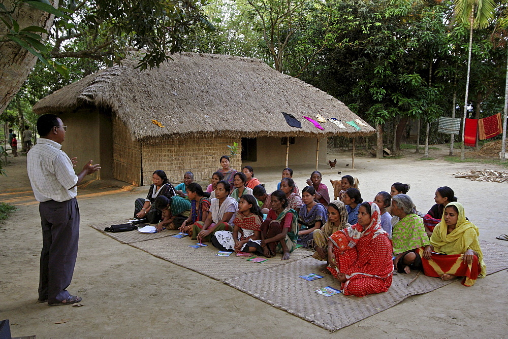 Bangladesh a group of women of the garo tribal minority attend a session of instruction about fish farming from a specialist at haluaghat, mymensingh region