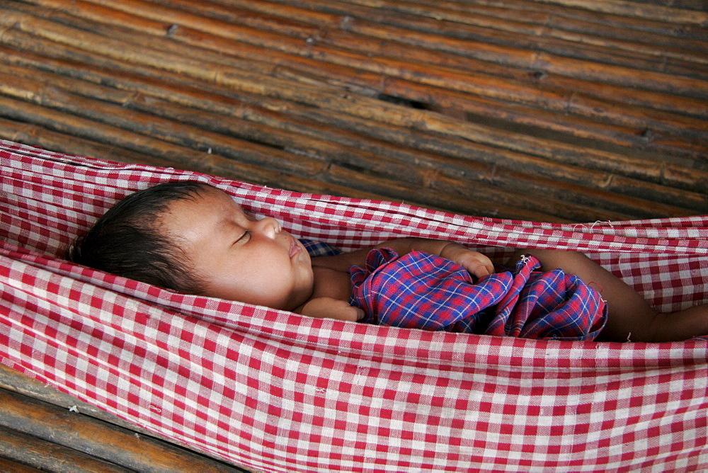 Cambodia baby asleep in hammock. Kampot province.