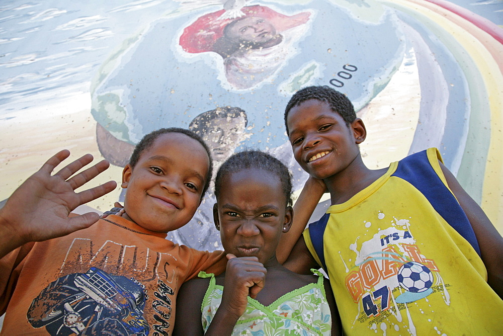 Namibia child at bernard nordkamp (youth) center, katatura, a black township of windhoek, dating from apartheid. country very high rates, mural behind depicts struggle against aids