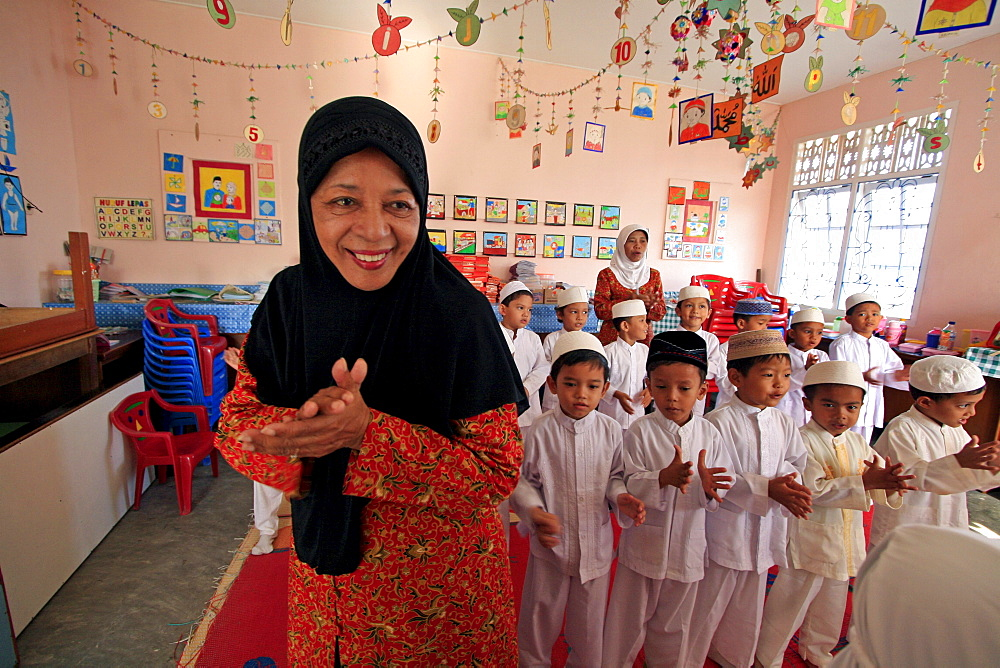 Indonesia a kindergarten in banda aceh which lost many of children to tsunami, been rebuilt. schools director halimah anwar bustam (seen here in foreground) describes horrors suffered: area kids came from completely flattened by waves. On that fateful sunday children were in their homes, or many were already on beach having. So many died that morning. It devastating. Only we getting things back together, very grateful to helping with reconstruction of damaged building. staff give up a portion of their (already) salaries to sponsor poor children from outlying villages to come to school. structure includes offices staff, a library, prayer room wheelchair accessible classroom.__ Photograph taken in banda aceh, -december 2006, 2 years after tsunami of december 26th 2004 devasted much of coastal region. Taken to illustrate reconstruction work projects of (catholic relief services) of sponsored photo tour