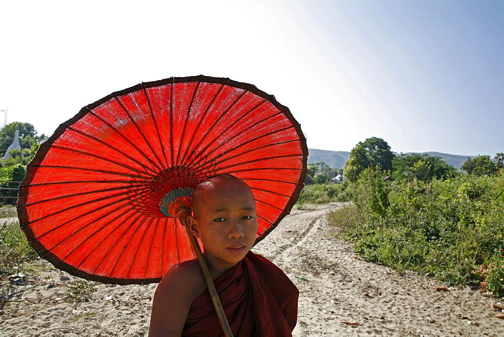 Myanmar monk with sunshade at white stupa, mingun, near mandalay