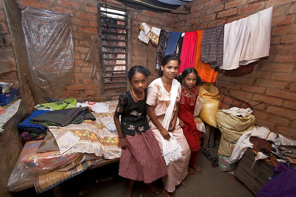 India. Small home of hindu family, omana radhara krishnan (mother) and her daughters rashmi (14) and maya (11). They will soon get a better house thanks to house building project funded by cnewa and implemented by diocese of kottayam social services in villages of wayanad district, kerala. 2007