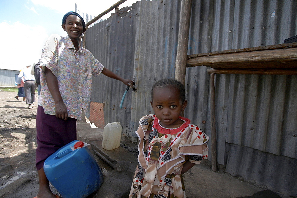 Kenya. Woman collecting water from public tap in mukuru ruben, a slum of nairobi