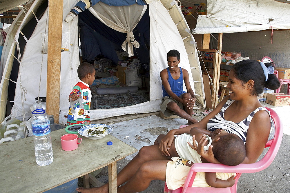 East timor. Family in front of their tent at the camp for internally displaced people (idps) located at the police academy in dili