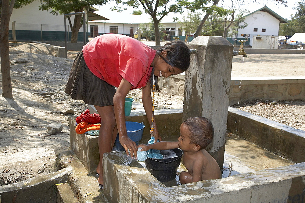 East timor. Camp for internally displaced people (idps) at the don bosco center in dili. Girl collecting water and washing baby at faucet