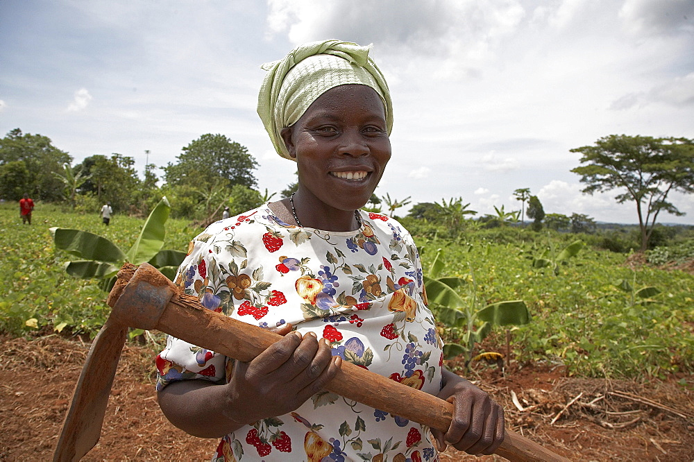 Uganda nejjemba teopista, farmer of kayunga and farmers group animator, holding her hoe after working in a communal garden at kangulumira where food is grown to feed the poor and sick. caritas uganda project