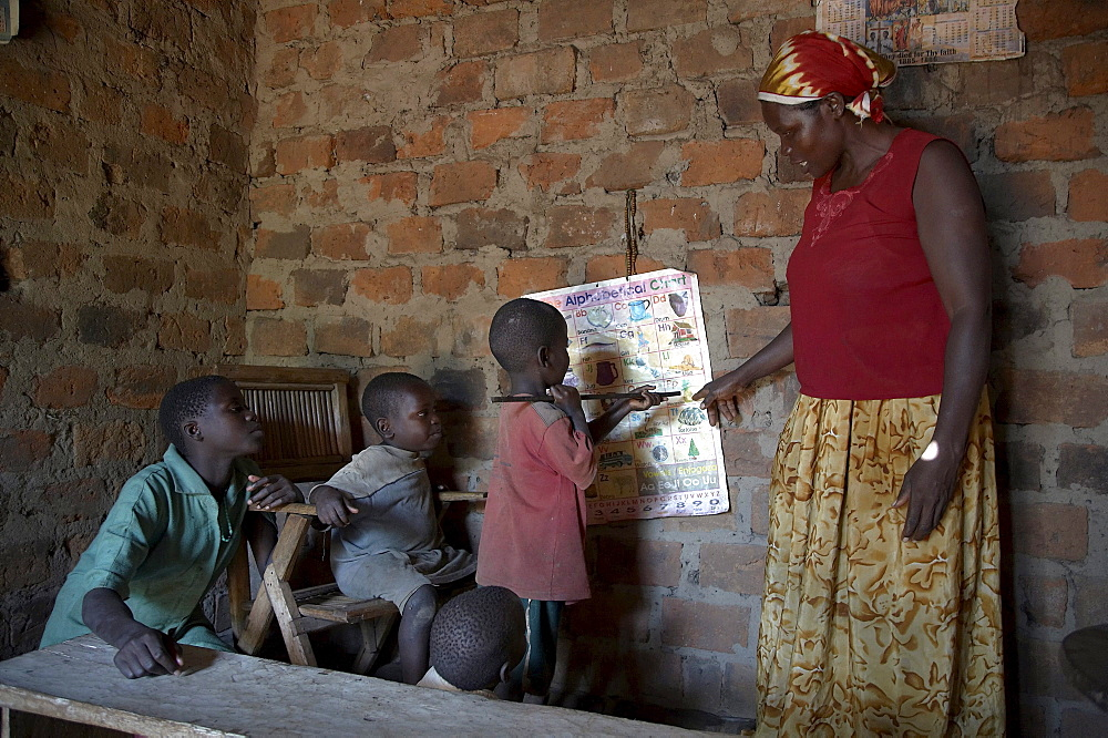 Uganda in the home of najjemba teopista, caritas lugazi agricultural field animator, kasaayi village, kayunga district. teopista teaching her children the abcs