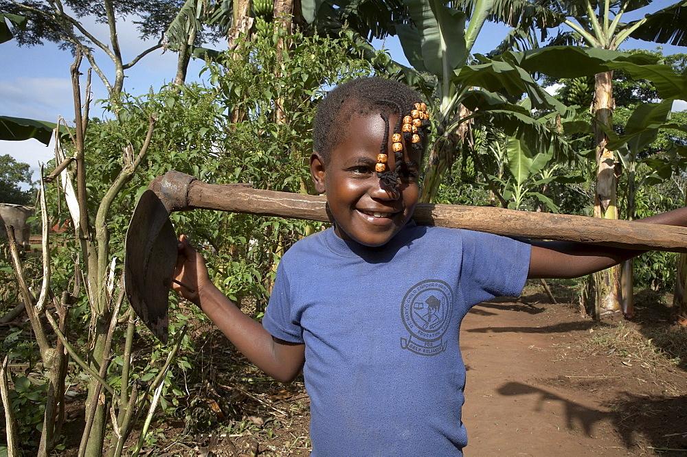 Uganda the home of ntanda miria, kayunga district. girl carrying hoe