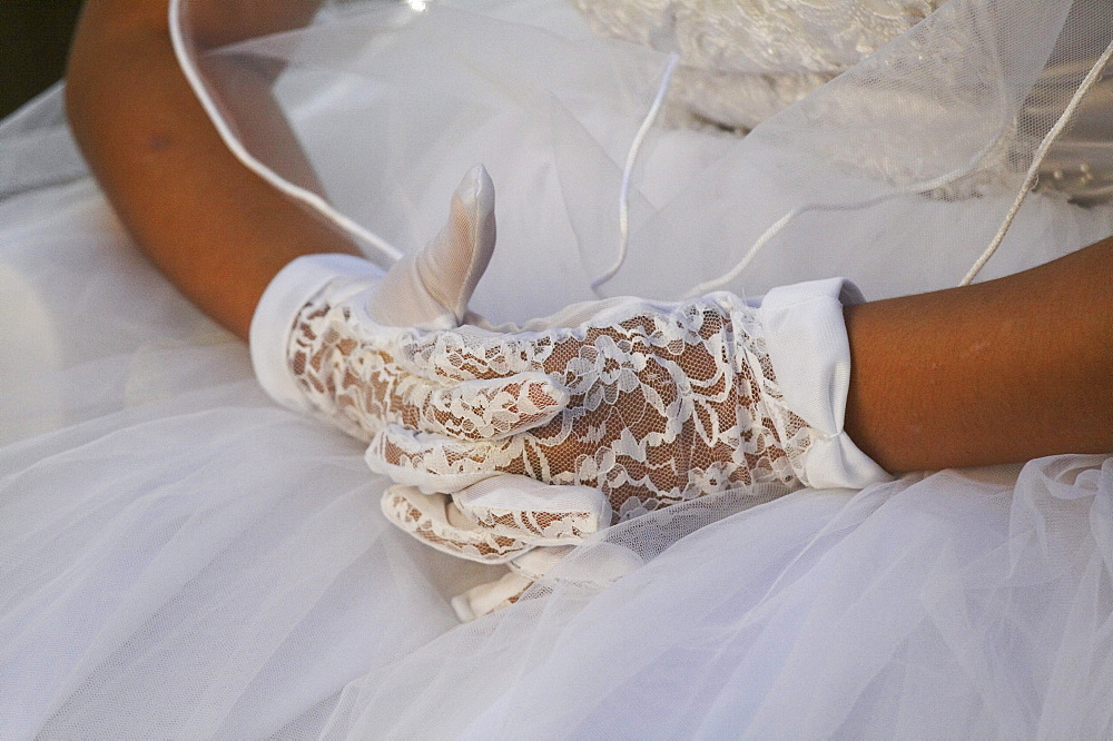 Guatemala catholic first communion and mass at remate, el peten. close-up of girls hands wearing lace gloves