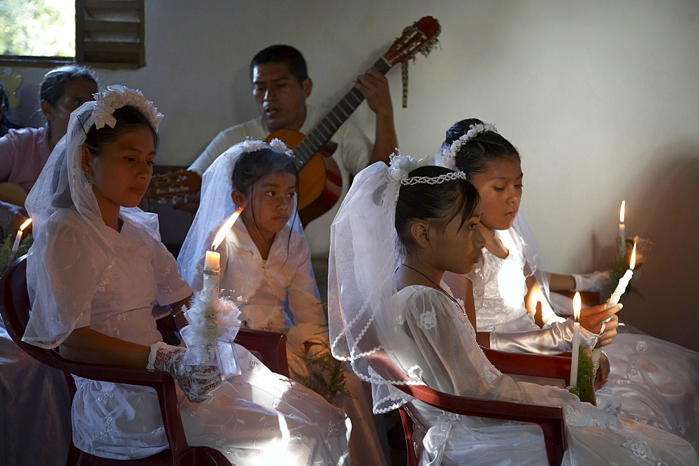 Guatemala catholic first communion and mass at remate, el peten. girls and musicians at ceremony