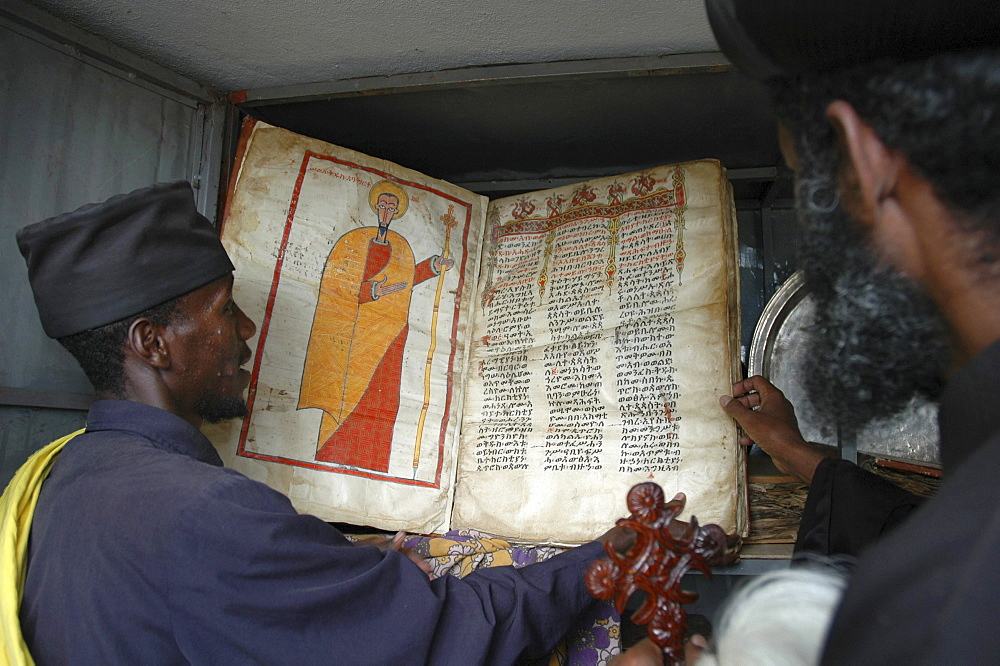 Religion, ethiopia. Orthodox archbishop gregorius visiting tullo gudo island and monastery of debre zion, lake ziway. Reading ancient parchment bibles and manuscripts stored in church.