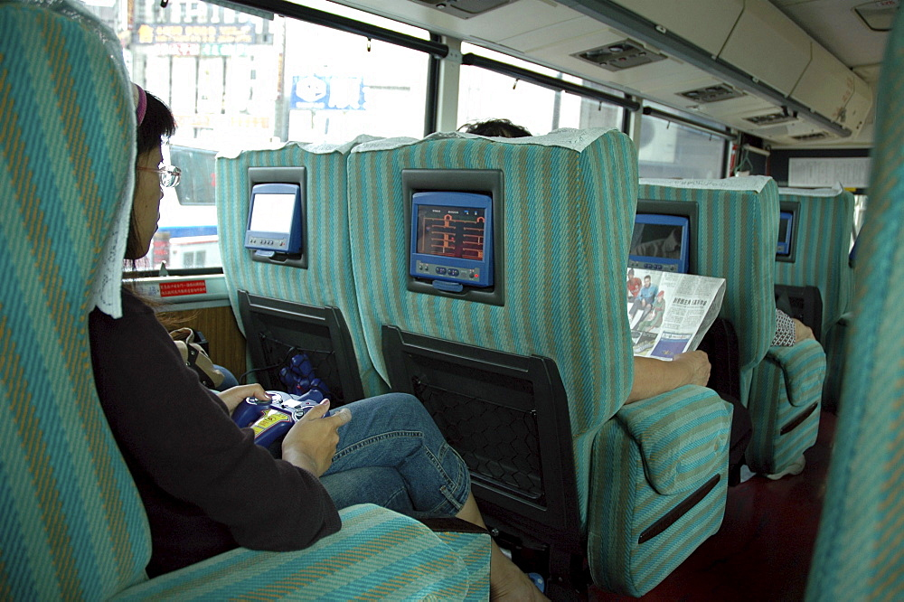 Transport, taiwan. Interior of inter-city bus, with video game and movie screens ay each seat