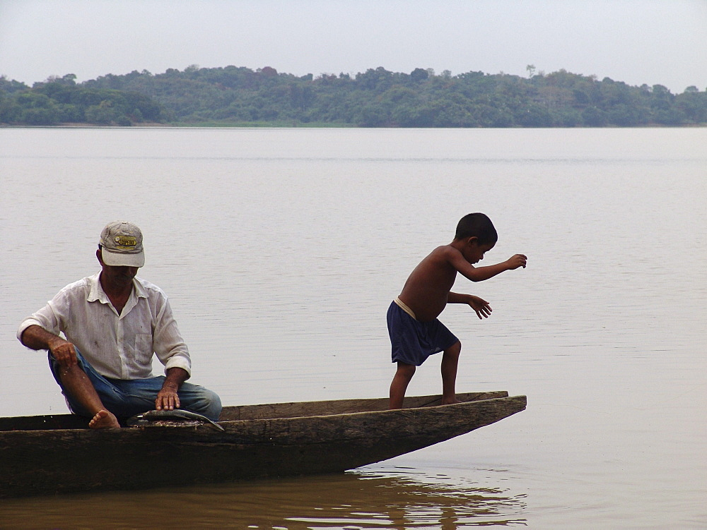 Colombia boy fishing from a dugout canoe in the rio magdalena, barrancabermeja
