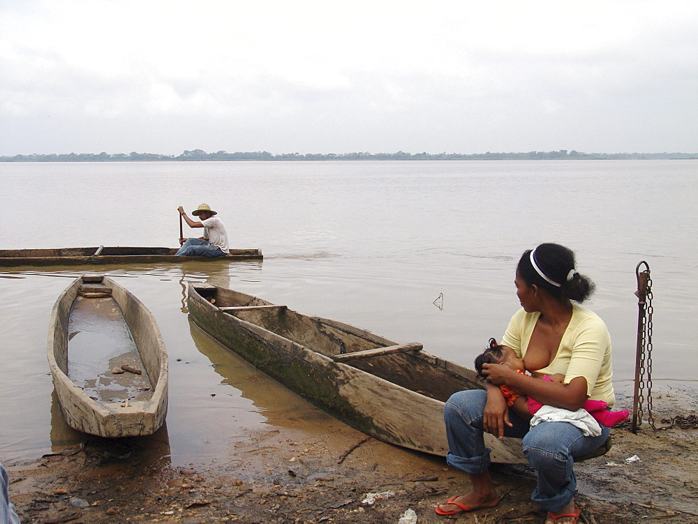 Colombia woman breast feeding her baby beside the rio magdalena, barrancabermeja. Fishermen go passed in a dug our canoe