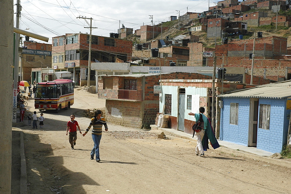 Colombia children running through the sprawling slum of altos de cazuca, bogota