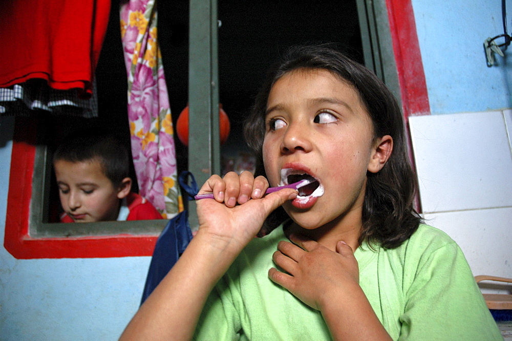 Colombia marly juliet, 7, of the slum of altos de cazuca, bogota, brushing her teeth