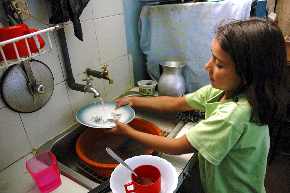 Colombia marly juliet, 7, of the slum of altos de cazuca, bogota, washing dishes
