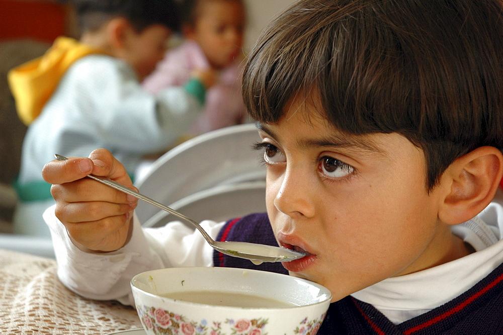 Colombia boy eating soup, ciudad bolivar, bogota