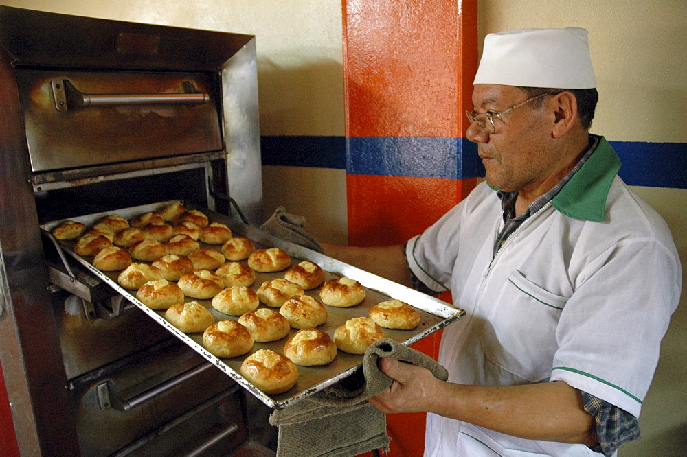 Colombia baker taking rolls out of the oven of his bakery in ciudad bolivar, bogota