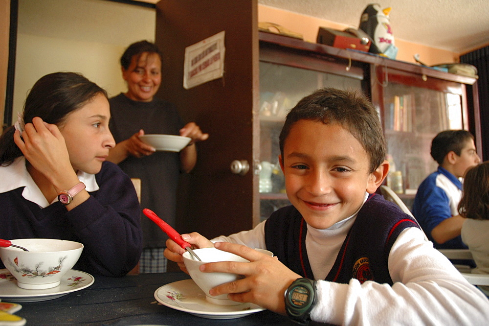 Colombia day in the life series: hugo andres, 7, of ciudad bolivar, bogota, with his sister a lineth, eating lunch at a soup kitchen for the poor