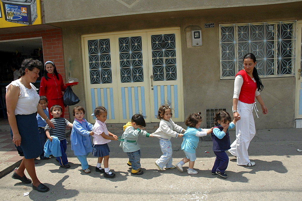 Colombia children in crocodile formation walking to their day care center, ciudad bolivar, bogota,