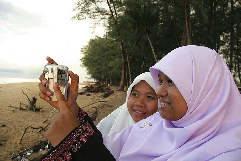 Thailand moslem girls with digital camera, songkhla beach photo sean sprague 2005