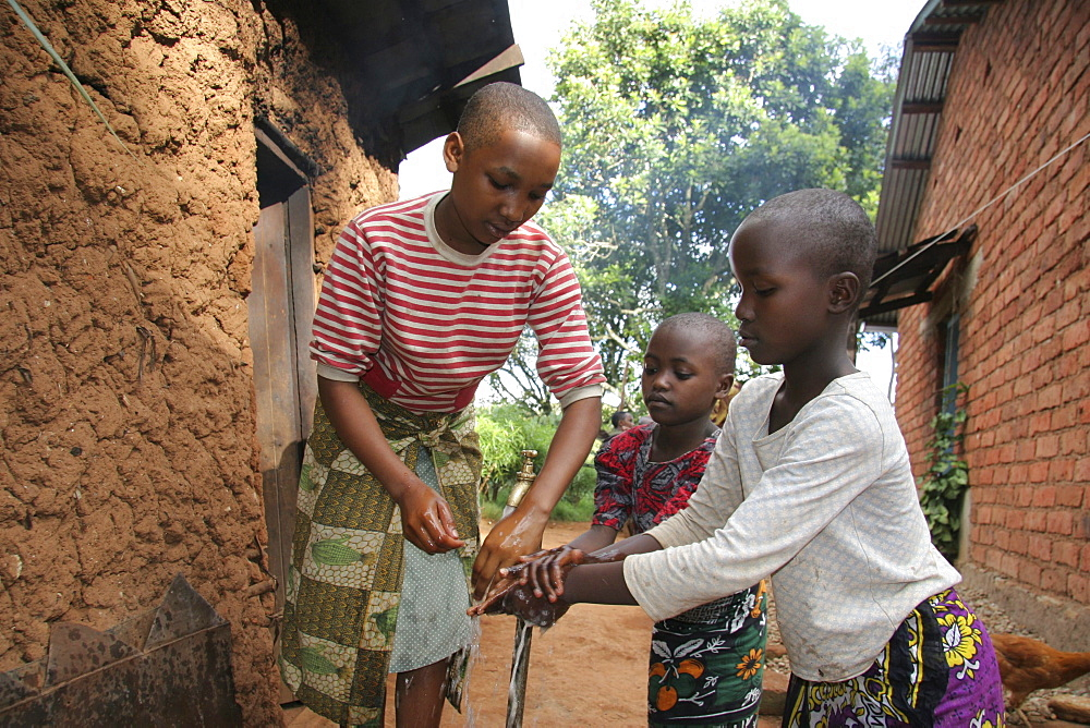 Tanzanian sisters washing their hands at the family tap. Mvango village, same, in the north-east near kilimanjaro