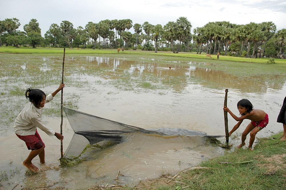 Cambodia girls fishing in village pond, kampong cham
