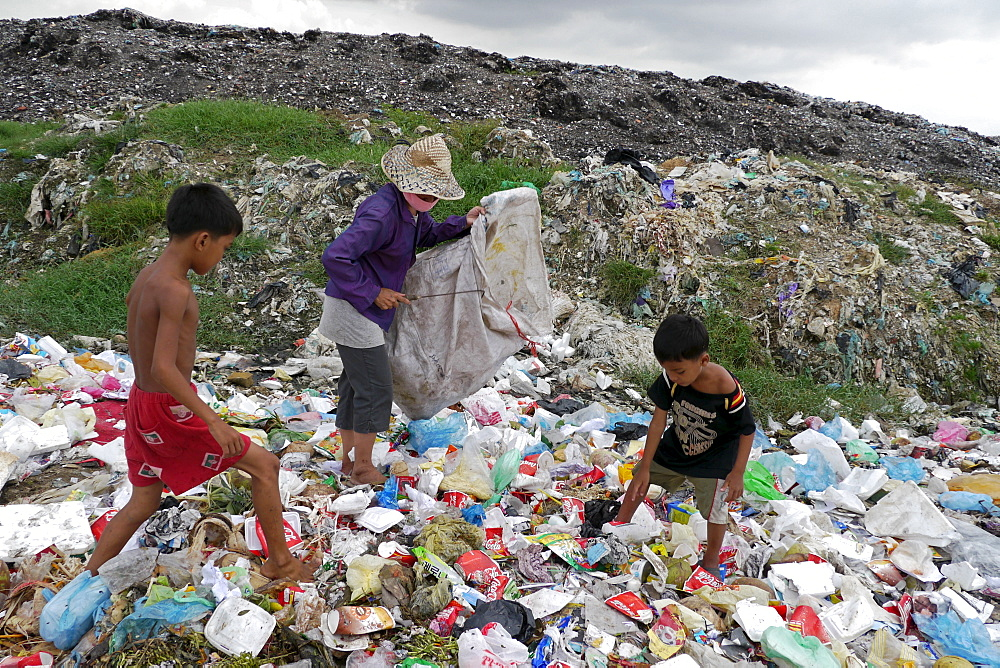 CAMBODIA Scavenger Soun Srey Thouch searching for recyclable materials on Phnom Penh's Mean Caeay garbage dump, with sons Khoeun Sovan (8) and Khoeun Sanja (10)