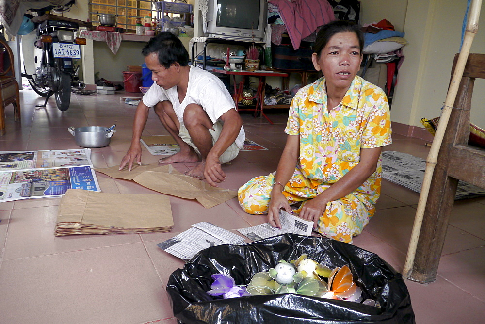 CAMBODIA HIV+ couple making handicrafts. Toul Sambo village is a resettlement area outside of Phnom Penh. Set in rural tranquility surrounded by paddy fields, it is a peaceful place for its residents. A Caritas Cambodia project, it has two focus groups who live there. One group is largely HIV+ and used to reside in a Phnom Penh slum called Borey Kila, until they were evicted by the government who wanted to develop the land for offices and shopping malls. The other group consists of those made homeless when a river's bank subsided in their village, destroying their homes. At the home of Kea Nimal and Kem Sokhorn, both HIV+. They are very industrious working at home making paper bags and ornaments, some with recyclable materials. They can earn $12-$15 per 5-day working week, and live quite comfortably in their attractive home with TV, motor-cycle and other conveniences. They say they are much better off than in the crowded and unhealth slum of Borey Kila in Phnom Penh where they used to live. They get regular orders for the handicrafts they make. They stay healthy by taking ARVs, which are supplied free of charge by the Hope Organization. PHOTO by Sean Sprague