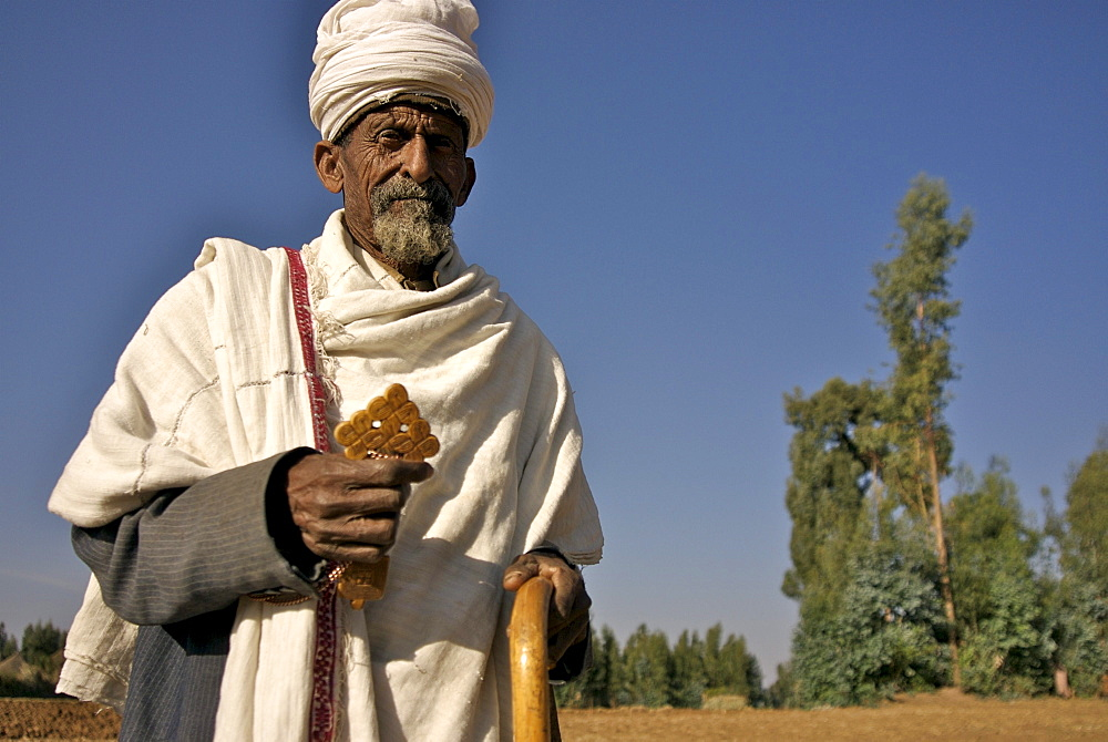 Old man, priest, in walking in the different villages of the hanamerant area,meket,ethiopia. He is people on his way . Ehtiopians are mainly christians with strong believe in angels. Ethiopia