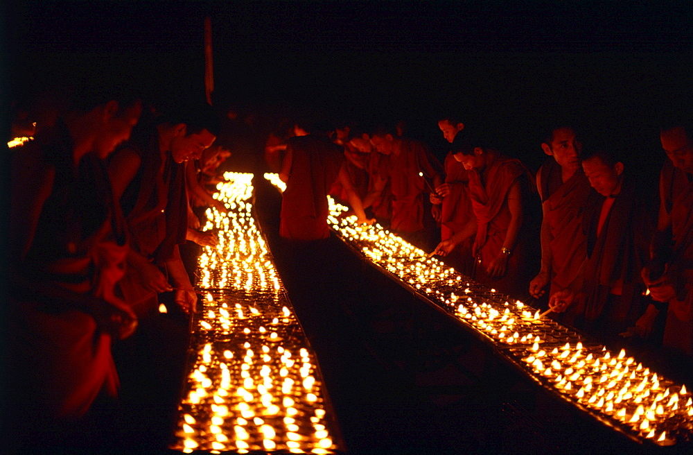 Monks offer butter lamps. Bodgaya, india. Monks offer butter lamps in front of mahabodhi temple marks site of buddhas enlightment twenty-five hundred years. centuries have made pilgrimages across himalayas to sites connected with life of historical buddha. From a tantric perspective, pilgrimage is more than paying homage at sacred sites. Rather, it is that activities performed at these places become a memory of place itself. By attuning oneself through ritual meditation to this timeless presence, similar experiences be evoked