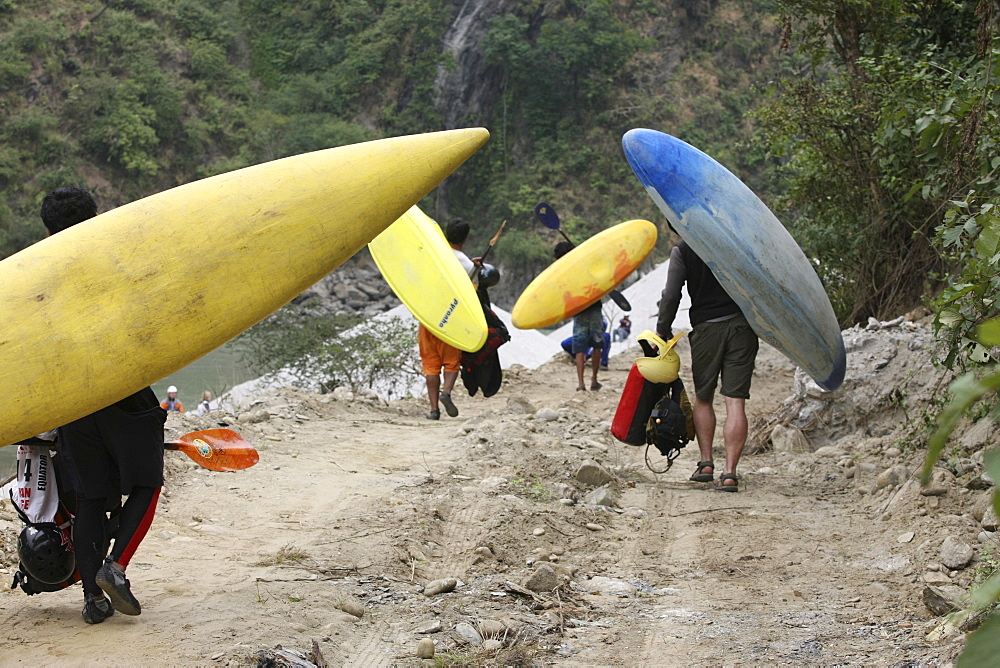 Paddlers carry their kayak to the start point for Downriver challenge. Paddlers race from a Le Mans style mass start, head to head down a stretch of challenging class 4 whitewater. Trisuli, Nepal