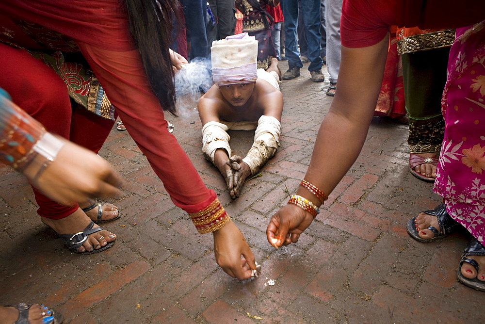 Some religious people reach Brahmayani temple measuring their body length. To do so, a person prostrates on the ground and extends his clasped hands above his head. An assistant puts a few grains of rice at the end of the clasped hands as a marking point. Then, the man steps to this marking point and then prostrates again. Bhaktapur, Nepal